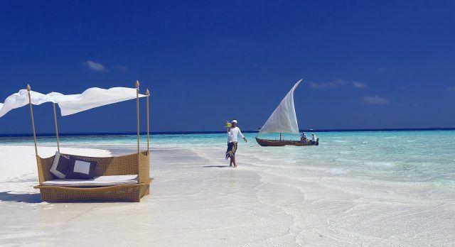 Person geht mit Getränken einen weißen Sandstrand auf den Malediven entlang
