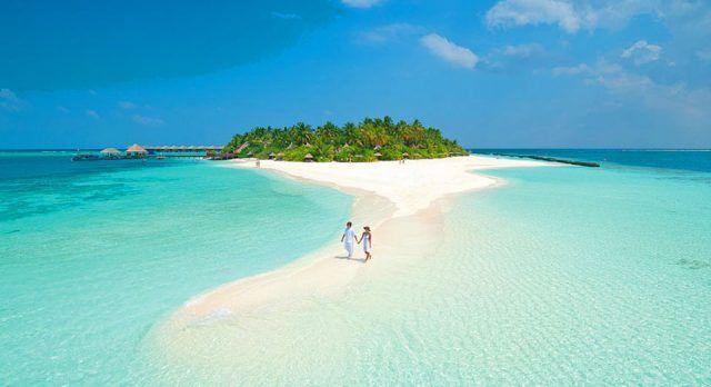 Paar in weißer Kleidung geht einen verlassenen Sandstrand auf den Malediven entlang