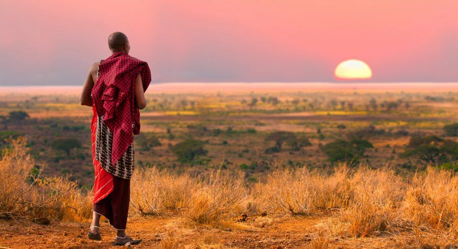 Traditionell gekleideter Mann in Tansania bewundert den Sonnenuntergang